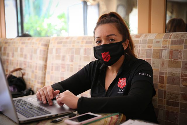 Woman with mask on working on computer