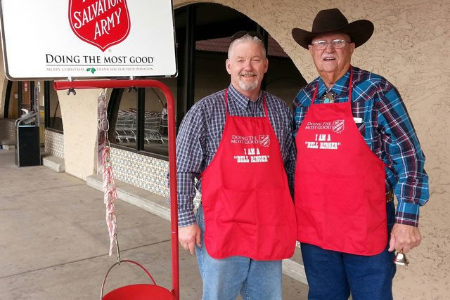 Two men with aprons next to red kettle