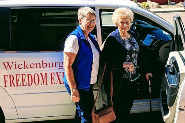"Two elderly women entering ""Freedom Express"" van"