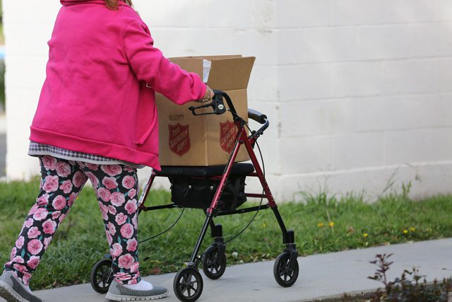 Woman walking with walker and box
