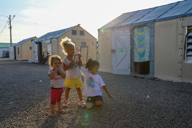 Three migrant girls outside in refugee camp