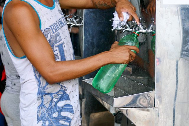 person filling up bottle with water