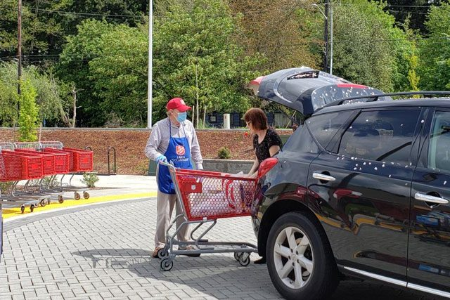 Man helping woman load trunk