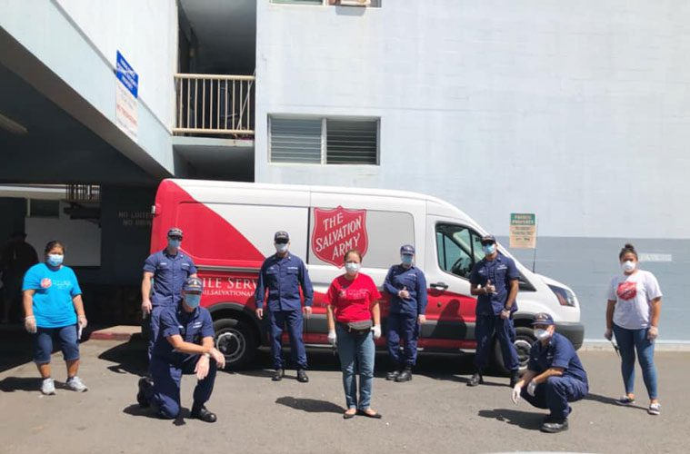Salvation Army workers standing in front of van